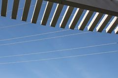 Oblique view looking up through slats of a pergola at blue sky and power lines. Copy space, horizontal aspect Royalty Free Stock Photo
