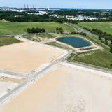 Obliquely taken aerial view of a construction site for a new development with a large filled rain retention basin royalty free stock photos
