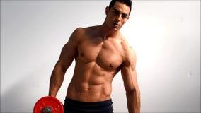 Obliques del entrenamiento del culturista y músculos masculinos hermosos jovenes del ABS con pesas de gimnasia, contra fondo liger