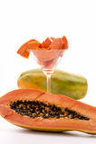 An oblong edible fruit - the Papaya. A longitudinal section through the globose body of a papaya fruit. Behind it, there is a cocktail glass filled with peeled Royalty Free Stock Image