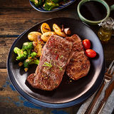 Oblong shaped plate with steak dinner. Top down view on oblong shaped plate with steak dinner. Includes side servings of broccoli, grilled potatoes and grape stock photos