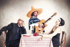 在晚餐的乏味夫妇oblyed听墨西哥音乐家 免版税库存图片
