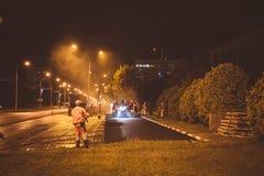 Obninsk, Rússia - em agosto de 2018: Pavimentação da noite do asfalto na estrada imagens de stock