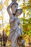Obninsk, Rússia - em outubro de 2017: Escultura do parque de uma mulher no estilo antigo com jarros e entre a folha do outono foto de stock royalty free