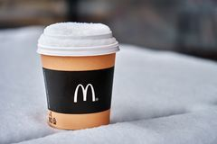 Obninsk, Russia - January 4,2019. Mcdonald`s paper cup of coffee standing on the table covered with snow royalty free stock photography