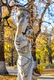 Obninsk, Russia - October 2017: Park sculpture of a woman in antique style with jugs and among autumn foliage royalty free stock image