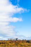 Obłoczny przód w niebie nad żółtymi drewnami i domami Zdjęcie Stock