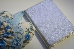 Obok notatnika z srebną pokrywą jest drukowany dekoracyjny ochraniacz fotografia stock