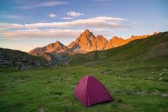 Obozować z namiotem na Alps Snowcapped pasmo górskie i sceniczny kolorowy niebo przy zmierzchem Przygoda i eksploracja podbija a, fotografia stock
