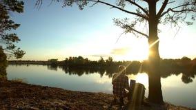 Obozowicz zdejmuje plecaka blisko lasowej rzeki, cieszy się zadziwiającego krajobraz, podwyżka fotografia stock
