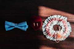 Obrączek ślubnych, motyla i podwiązki panna młoda na drewnianym stole, fotografia royalty free