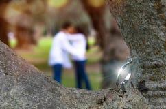 Obrączka ślubna dla państwa młodzi dzień ślub W tło pary unfocused całowaniu w parku obraz royalty free