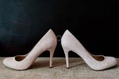 Obrączka ślubna między panny młodej ` s butami na ciemnym tle Fotografia Royalty Free