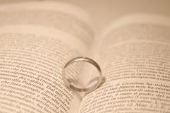 Obrączka ślubna na biblii książce Obrazy Stock