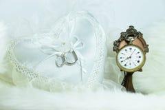 Obrączka ślubna na kierowej poduszce, zegar na miękkiej tkaninie zdjęcie stock