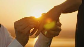 Obrączka Ślubna Stawiająca Na Palcowych rękach Dotyka zmierzch panny młodej fornala mężczyzna kobiety małżeństwa propozyci wakacj zbiory