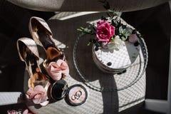 Obrączki ślubne, bukiet lawendowi i beżowi drużka buty zdjęcia stock