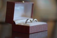 Obrączki ślubne dla ona i on, set w eleganckim Burgundy skóry pudełku fotografia royalty free