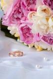 Obrączki ślubne i bukiet Zdjęcia Royalty Free