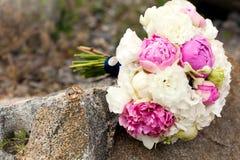 Obrączki ślubne kłamają na kamieniu przed bukietem kwiaty obraz royalty free