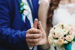 Obrączki ślubne na śmiesznych kciukach Obrazy Stock