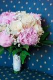 Obrączki ślubne na bukiecie peonie i róże na błękitnym tle Zdjęcie Royalty Free