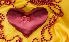 Obrączki ślubne na czerwonym atłasowym sercu na żółtym tle Fotografia Royalty Free