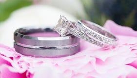Obrączki ślubne nad kwiatem zdjęcia royalty free