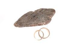 Obrączki ślubne obok kamienia na białym tła odosobnieniu Zdjęcia Royalty Free