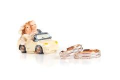 Obrączki ślubne obok zabawkarskiego czekoladowego maszynowego odosobnienia na whi Obrazy Stock