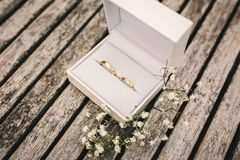 Obrączki ślubne w pudełku na stole mali kwiaty na drewnianym stole obrazy royalty free