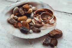 Obrączki ślubne w skorupie pełno denni otoczaki na białym tle fotografia stock