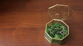 Obrączki ślubne w szkła pudełku wypełniali trawy na stole zbiory