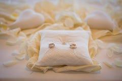 Obrączki ślubne wraz z białą arkaną na białej poduszce otaczali białych serca Małżeństwo ceremonia fotografia royalty free