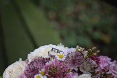 Obrączki ślubne z ślubnym bukietem, selekcyjna ostrość Obrazy Royalty Free