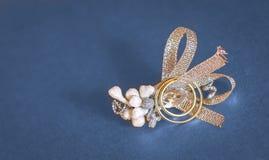 Obrączki ślubne z biżuterii dekoraci błękita tłem Zdjęcia Royalty Free