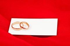 Obrączki ślubne z kartą na czerwonej tkaninie Zdjęcie Stock