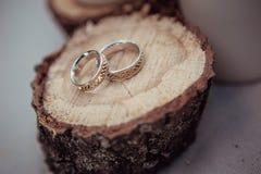 Obrączki ślubne z pięknymi cyzelowaniami na tle piłująca drewniana i bieliźniana tkanina, zakończenie obrazy stock