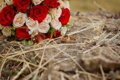Obrączki ślubne zbliżają bukiet róże Fotografia Stock