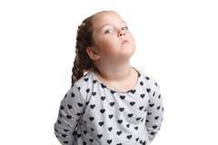 Obrażająca mała dziewczynka, z przykrością trzyma ręki za plecy pojedynczy białe tło fotografia stock