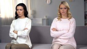 Obrażający żeńscy przyjaciele siedzi z rękami krzyżowali na różnych częściach kanapa zdjęcia stock