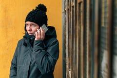 Obrażona kobieta podczas rozmowy telefoniczej na ulicie w zimie zdjęcie royalty free
