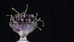 Obracanie rozsypisko ciemne wiśnie w szklanej wazie zbiory