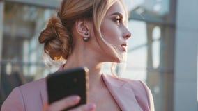 Obracanie widok młodej blondynki biznesowa dama uśmiecha się jej telefon i używa w jaskrawym świetle słonecznym nowożytne technol zbiory wideo