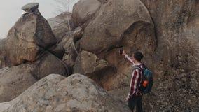 Obracanie widok młody elegancki mężczyzna w w kratkę koszula z plecakiem bierze selfie otaczającego z, wysokie skały zbiory