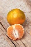 Obrany tangerine i tangerine plasterki na drewnianym stole Obrazy Royalty Free