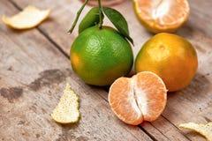 Obrany tangerine i tangerine plasterki na drewnianym stole Obraz Stock