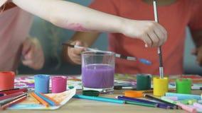 Obraz lekcje przy dziecko sztuki klubem Dzieciaki stawia paintbrush w wodnego szkło zbiory wideo
