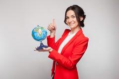 Obrazek ładna kobieta w czerwonym blezerze z ziemską sferą w rękach Obrazy Royalty Free