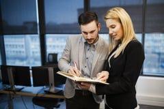 Obrazek biznesmen i bizneswoman patrzeje notatnika fotografia royalty free